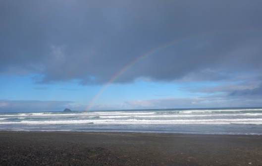 Beautiful rainbow over a black sand beach